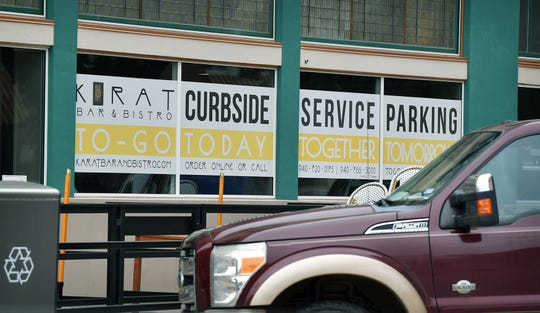 A large banner indicates the provision of curbside order pickup at the Karat Bar & Bistro downtown.