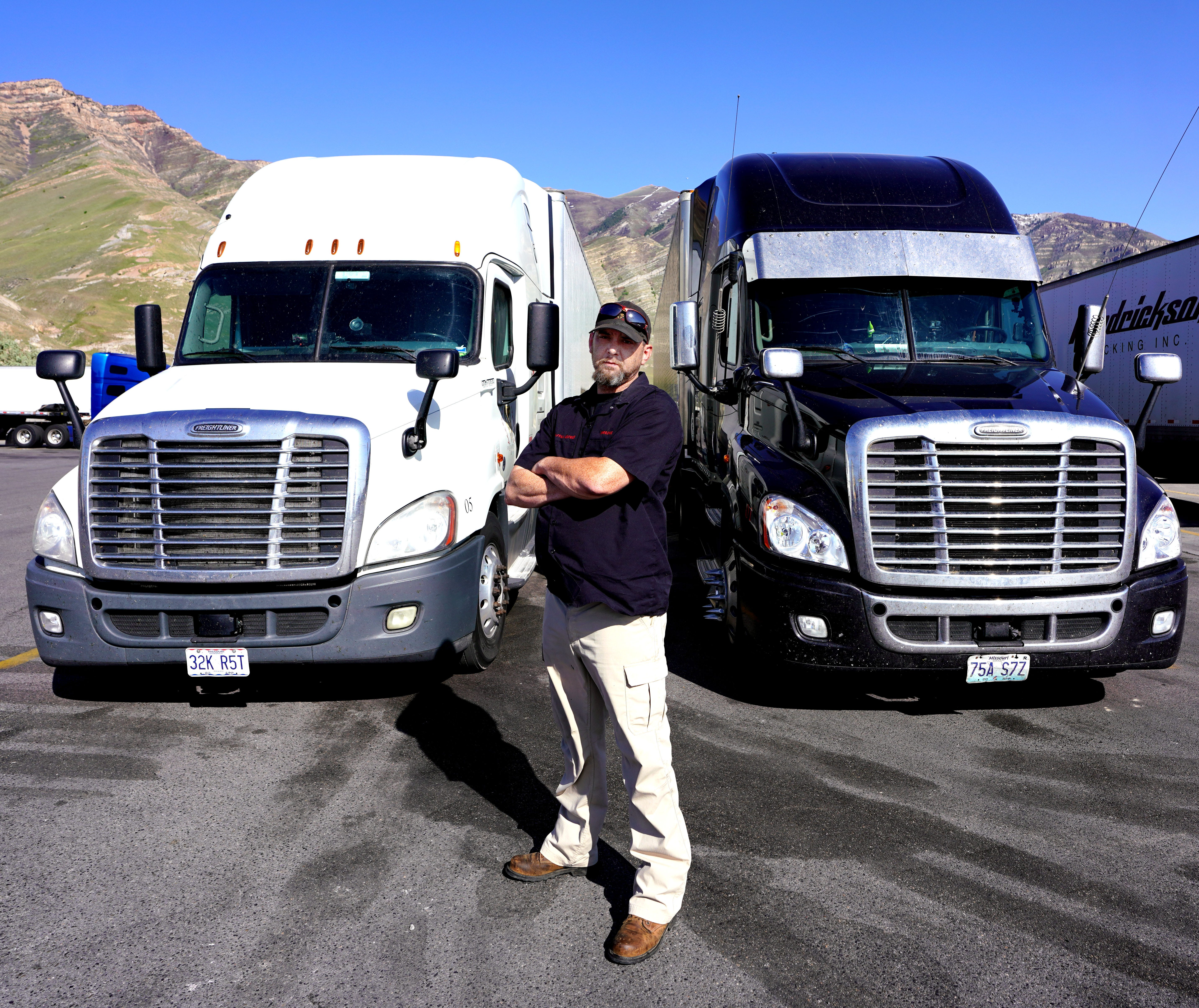 Trucker James Rodgers stands in front of two of his trucks at a truck stop outside Salt Lake City.
