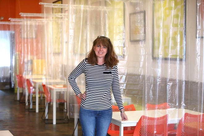 Kim Shapiro, co-owner of Twisted Citrus, is shown in her restaurant in North Canton, Ohio, on Thursday, May 7, 2020. In anticipation of restaurants reopening, the owners have reconfigured seating and hung clear plastic shower curtains between tables for protection.