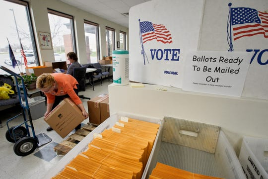 In this April 14, 2020 photo, Nadette Cheney picks up a box of printed ballots as others work on preparing mail-in ballots at the Lancaster County Election Committee offices in Lincoln, Neb. Officials in Nebraska are forging ahead with plans for the state's May 12 primary despite calls from Democrats to only offer voting by mail and concerns from public health officials that in-person voting will help the coronavirus spread.  (AP Photo/Nati Harnik) ORG XMIT: NENH208