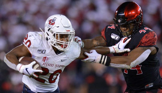 Fresno State RB Ronnie Rivers (20) is defended by San Diego State LB Kyahva Tezino during the Aztecs' 17-7 win last season.