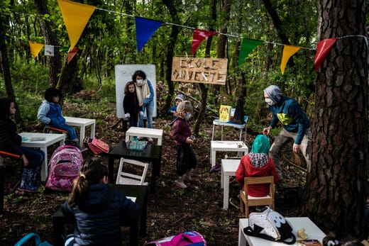 Children attend a course in the forest near Upie, France on May 12, 2020. - Some pupils went to school again amongst oaks and pines with parents acting as teachers as a protest schools remaining closed in the village.