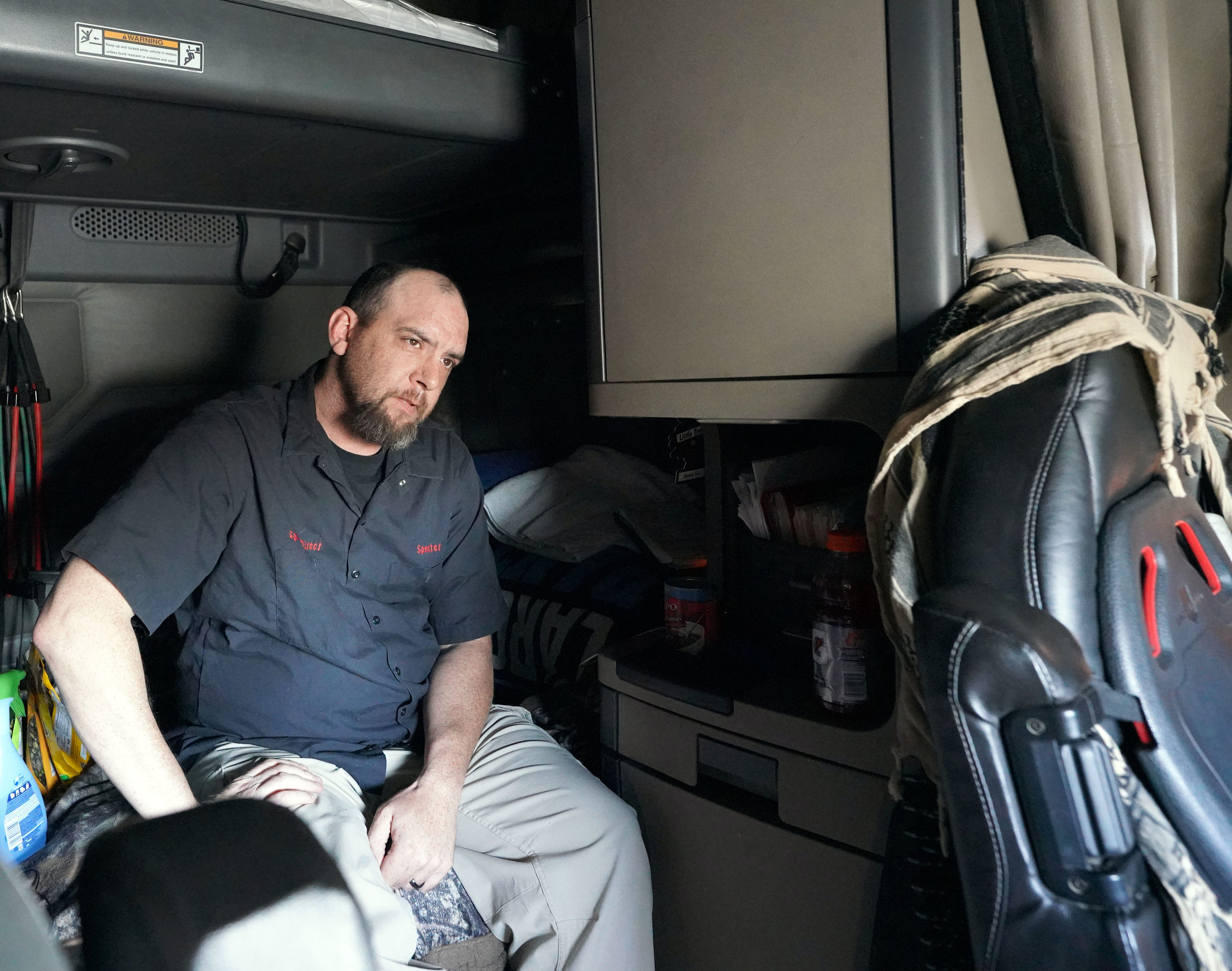 Trucker James Rodgers sits quietly in the cab of his Freightliner after kicking off his steel-toed boots following a long day of driving across Wyoming and to Salt Lake City