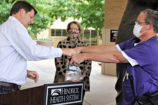 U.S. Rep. Jodey Arrington, left, takes a face mask from a sealed bag from Greg Perry, pharmacist and clinical manager of pharmacy at Hendrick Medical Center before entering the hospital Wednesday. Looking on is Elizabeth Henry, director of case management. There is strict enforcement of health protocol at the hospital, which has treated COVID-19 patients.
