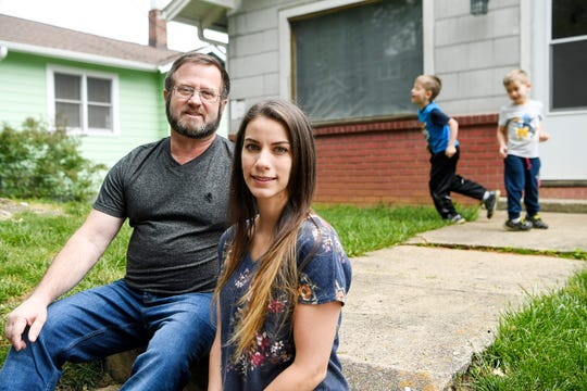 Michael and Harmony Owen pose for a photo as their children play in West Asheville May 13, 2020.