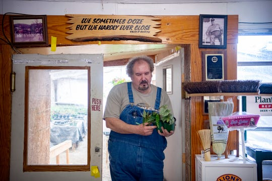 Wade McCourry walks through a set of double doors with plants for a customer below a sign that his dad, Troy, had made as he works at the business he inherits from him, Troy's Greenhouse and Garden Supply in Burnsville on May 13, 2020. The sign was something his dad had said to a customer on the phone who called during a holiday season many years ago. A photo of Troy McCourry hangs on the wall to the right.