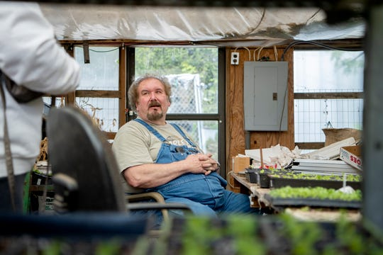 """Wade McCourry talks to a customer about why her plants may have died as he works at his business, Troy's Greenhouse and Garden Supply, in Burnsville on May 13, 2020. """"I probably get more calls than the county agent,"""" he said about being seen as a community resource for gardening knowledge."""