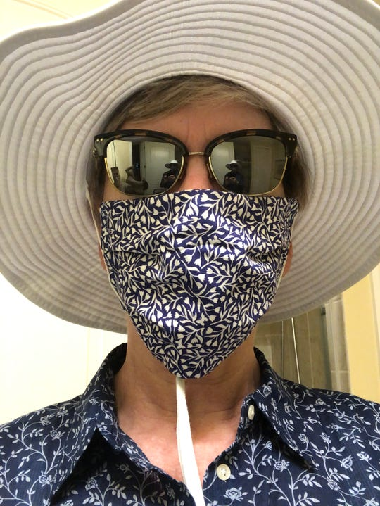 Cindy Holmes is a former TODAY writer from Cocoa Beach who wears a mask to walk on the beach.