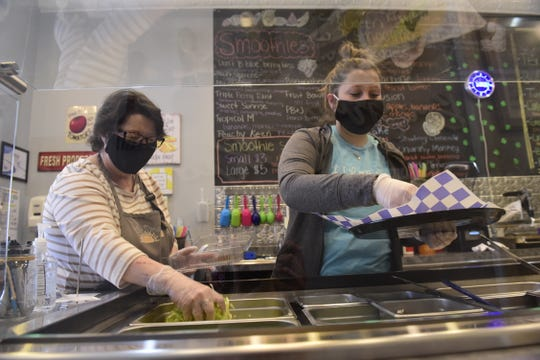 Rhonda Rohrer, left, and Payton Miller wears masks as they prepare meals Wednesday at Fit Fab Fun in Bucyrus.