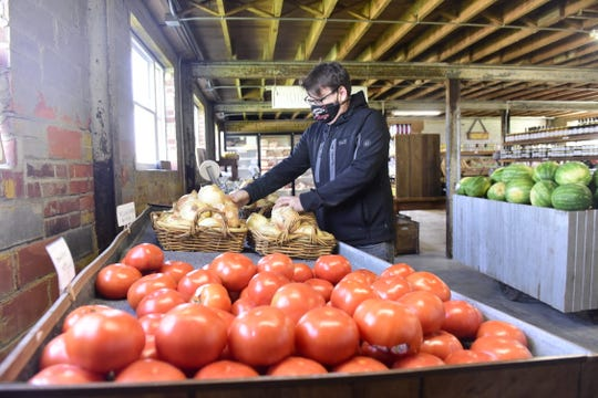 Chris Schimpf of Pickwick Place stocks a few onions Wednesday during the shop's first day of business.