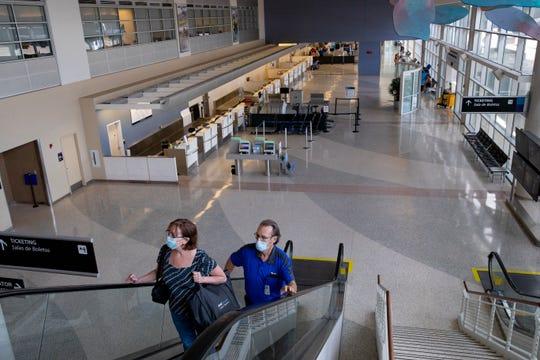 People ride the escalator to the TSA checkpoint inside Corpus Christi International Airport on Wednesday, May 13, 2020.