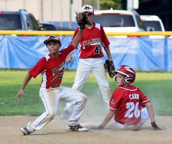 Mount Laurel's Anthony Masciulli waits for the call after applying a tag to Will Carr of the Marlton Reds in a 2017 Cal Ripken baseball tournament game.