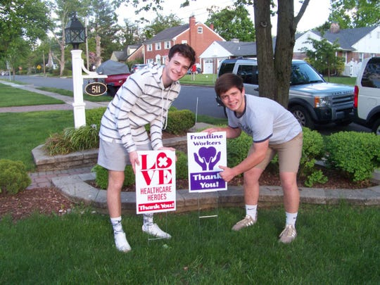Jesse Lang, left, and brother J.R.. post signs that their Haddon Township family designed and had manufactured to sell to homeowners for the benefit of front line workers in the fight  against the coronavirus pandemic.