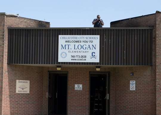 An investigator takes pictures of the damage and scorched walls caused by a fire that broke out on top of the roof of Mt. Logan Elementary on May 13, 2020. According to the Chillicothe City School District Facebook page, the fire caused minimal damage with no injures and is still under investigation.