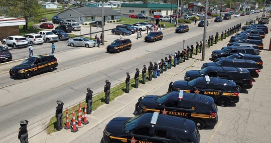 "As fellow sheriffs from around the state salute, cruisers from the Pickaway County Sheriff's Department lead the funeral procession for former Sheriff Dwight Radcliff Wednesday afternoon in Circleville, Ohio. Radcliff was the 37th sheriff of Pickaway County, serving 48 years until he chose not to seek re-election in 2012. The longtime sheriff died last week at the age of 87. He was a second-generation sheriff, with his father having served before him. Son Robert ""Robbie"" Radcliff succeeded him.   (Doral Chenoweth/Columbus Dispatch)"