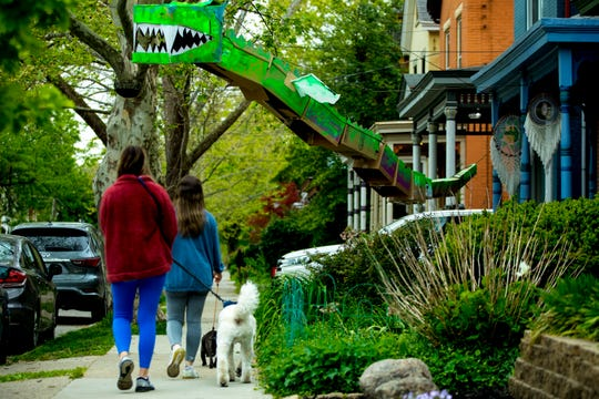 "Pedestrians walk their dogs past a ""ScareCoronas"" sculpture on display in Northside on Wednesday, May 13, 2020. The ""ScarCoronas"", a variation on the classic scarecrow, were made by residents of north side as part of a walking art show that kicked off on May 7 and runs until May 21.."