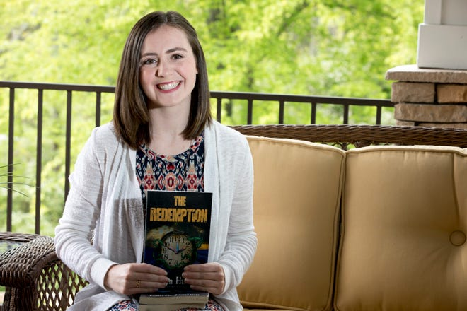 "Lauren Hudson sits outside her home in Villa Hills, Kentucky holding her book series entitled ""The Ascension Series."" ""The Redemption,"" which is the third and final installment, has just been released."