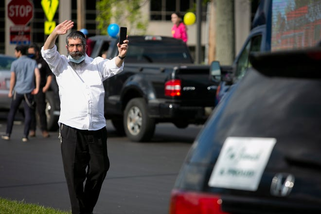 "Rabbi Yisroel Mangel waves to members of the Blue Ash police and fire department during the Chabad Jewish Center's Lag BaOmer Car Parade on Tuesday, May 12, to honor local first responders and essential workers during the new coronavirus pandemic. ""Lag BaOmer actually commemorates the end of a plague/pandemic that claimed 24,000 lives, students of the great sage Rabbi Akiva, 2000 years ago in Biblical Israel. The plague ended when they increased their mutual love and unity. Its meaning is so relevant to us all,"" said Rabbi Mangel, director of Chabad Jewish Center."