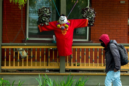 "A pedestrian walks passed a ""ScareCoronas"" sculpture on display on Chase Street in Northside on Wednesday, May 13, 2020. The ""ScarCoronas"", a variation on the classic scarecrow, were made by residents of north side as part of a walking art show that kicked off on May 7 and runs until May 21."