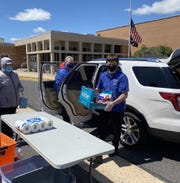 Volunteers unload non-perishable food from an SUV outside Edison High School.