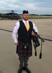 Wearing the full uniform of the Homeland Security Investigations Pipe Band, Mike Glackin stands in front of a Black Hawk helicopter at Washington Dulles International Airport.