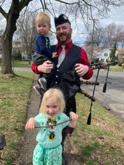 Mike Glackin holds his son Gavin and stands behind his daughter Lily in front of the family's Cranford home on St. Patrick's Day.