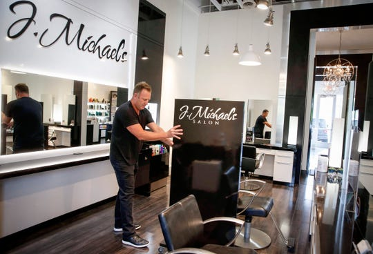 Jay Ryan moves a mobile partition into the salon at J Michaels Salon while getting ready to reopen this weekend in Des Moines.