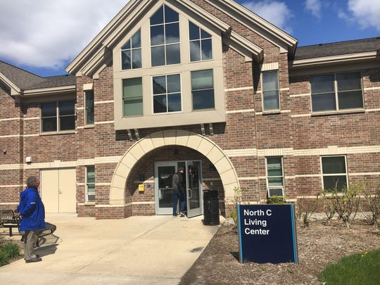 Andy Beachnau, associate vice provost of student affairs and director of housing and health services at Grand Valley State University, waits for another staff member to enter a living center on Grand Valley's Allendale campus on Monday, May 11.
