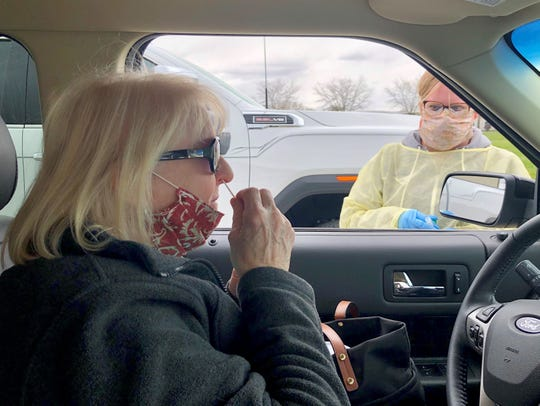 Diane Jordan swirls a swab in her nose, collecting a sample for COVID-19 testing as Heather Rogal, a medical assistant, offers instructions at the drive-up testing clinic on Grosse Ile on Saturday, May 9, 2020.