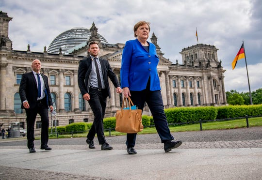 Chancellor Angela Merkel (CDU) walks to the Chancellery on foot, accompanied by her bodyguards, after the government questioning in the Bundestag in Berlin, Germany, Wednesday, May 13, 2020.