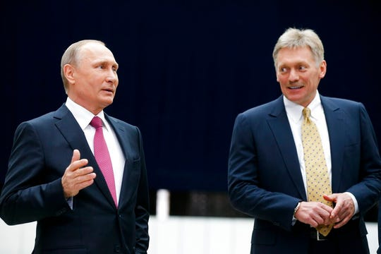 In this Thursday, June 15, 2017 file photo Russian President Vladimir Putin speaks to the media after his annual televised call-in show as his press secretary Dmitry Peskov, right, smiles in Moscow, Russia. Peskov said Tuesday May 12, 2020, that he is hospitalized with the coronavirus. The announcement comes just a day after Putin said Russia was successful in slowing down infections and announced easing some of the nationwide lockdown restrictions.