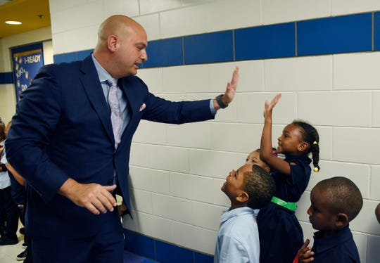 FILE - Superintendent Nikolai Vitti high fives Caimile Moreland, 5, in the hallway during his visit at Schulze Elementary School.