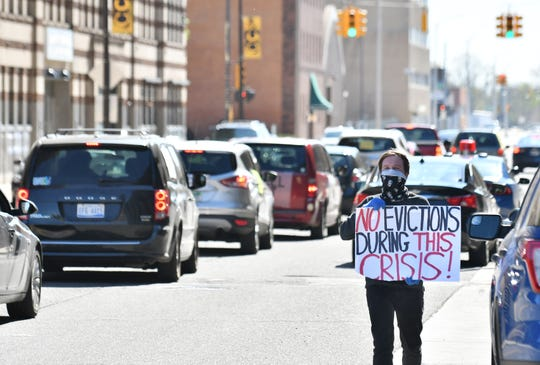 Organizer Joe McGuire walks and holds a sign while people drive their vehicles around Cadillac Place as part of a caravan protest organized by Detroit Eviction Defense in Detroit on May 13, 2020.