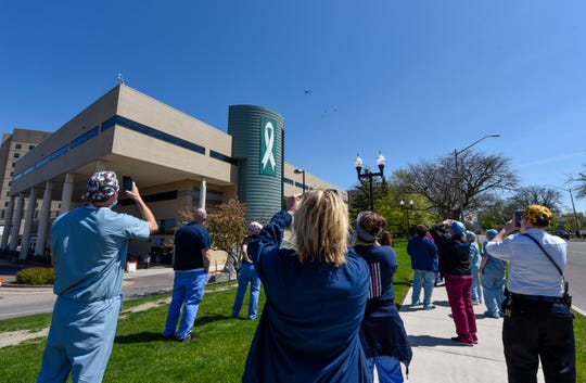 Hospital workers watch as a KC-135 Stratotanker and three A-10 Thunderbolt II planes with from the Michigan Air National Guard pass over Henry Ford Hospital in Wyandotte, Wednesday.