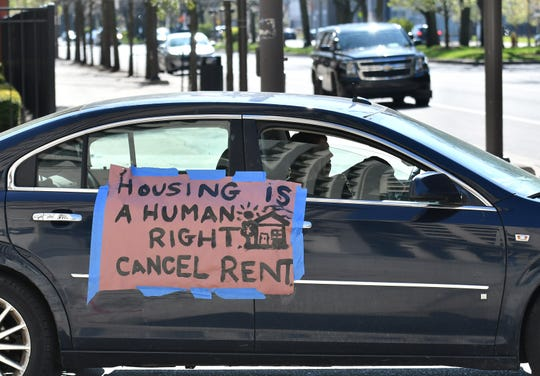 Kathryn Nowinski, 29, of Detroit drives around Cadillac Place as part of a caravan protest organized by Detroit Eviction Defense in Detroit on May 13, 2020. The group calls for extending the eviction ban until at least 60 days have passed after the end of the current state of emergency.