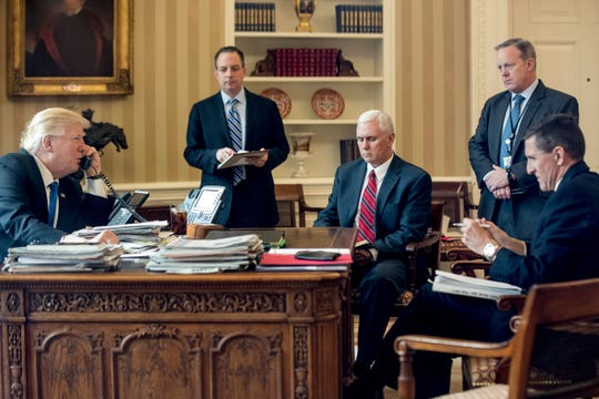 In this Jan. 28, 2017, file photo, President Donald Trump accompanied by, from second from left, Chief of Staff Reince Priebus, Vice President Mike Pence, White House press secretary Sean Spicer and National Security Adviser Michael Flynn speaks on the phone with Russian President Vladimir Putin in the Oval Office at the White House in Washington.