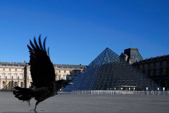In this Monday, March 30, 2020 file photo, a black crow flies over in the deserted Louvre museum courtyard in Paris. The European Union unveiled Wednesday May 13, 2020, its plan to help confinement-tortured citizens across the 27 nations salvage their summer vacations after months of coronavirus lockdown and resurrect Europe's badly battered tourism industry.