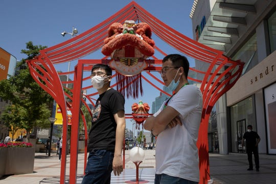 Residents wear masks against the coronavirus as they visit a retail district in Beijing on Tuesday, May 12, 2020. Shares were mostly lower Tuesday in Asia as worries over fresh outbreaks of coronavirus cases overshadowed hopes over reopening economies.