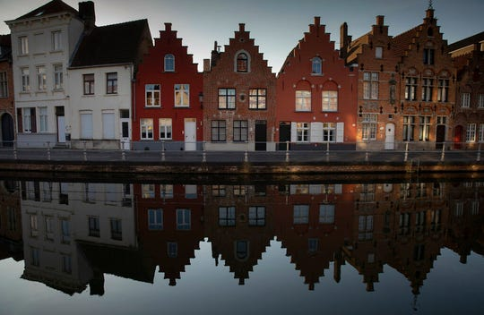 Houses make a reflection on the water in Bruges, Belgium, during a partial lifting of a lockdown to prevent the spread of coronavirus, COVID-19, Wednesday, May 13, 2020.
