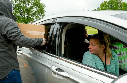 Helfrich Park STEM Academy student Brylee Herron looks back as meal kits are loaded into the car at Central High School Wednesday morning, May 13, 2020. This was her first time receiving the meal kits prepared by AmeriQual.