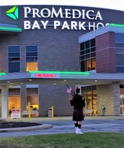 Bill Poiry plays bagpipes at sunset at Bay Park Hospital