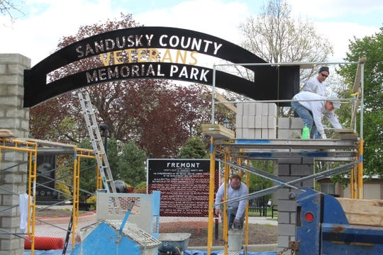 A crew from Lochotzki Masonry LLC work on two new stone columns with an archway being installed at Sandusky County Veterans Memorial Park in Fremont.