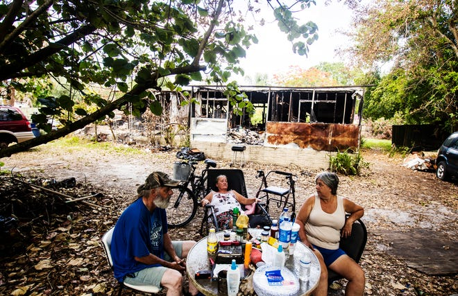 From left, Richard Fairchild, Sandra Robinson and his sister, Marian Hagen sit in front of the Suncoast Estates trailer they inhabited in North Fort Myers on Tuesday May, 12, 2020. The trailer was destroyed in a fire several weeks ago. They are staying in a pop-up camper in front of the property that Richard bought with his last paycheck.