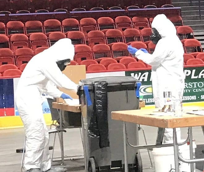 Workers in Tyvek suits at Brown County's COVID-19 testing station at the Resch Center on Wednesday, May 13.