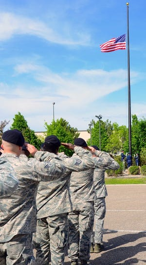 Airmen with the 341st Security Forces Group salute during a retreat ceremony May 16, 2016, at Malmstrom Air Force Base, Mont. Great Falls was recognized as a 2021 Great American Defense Community.