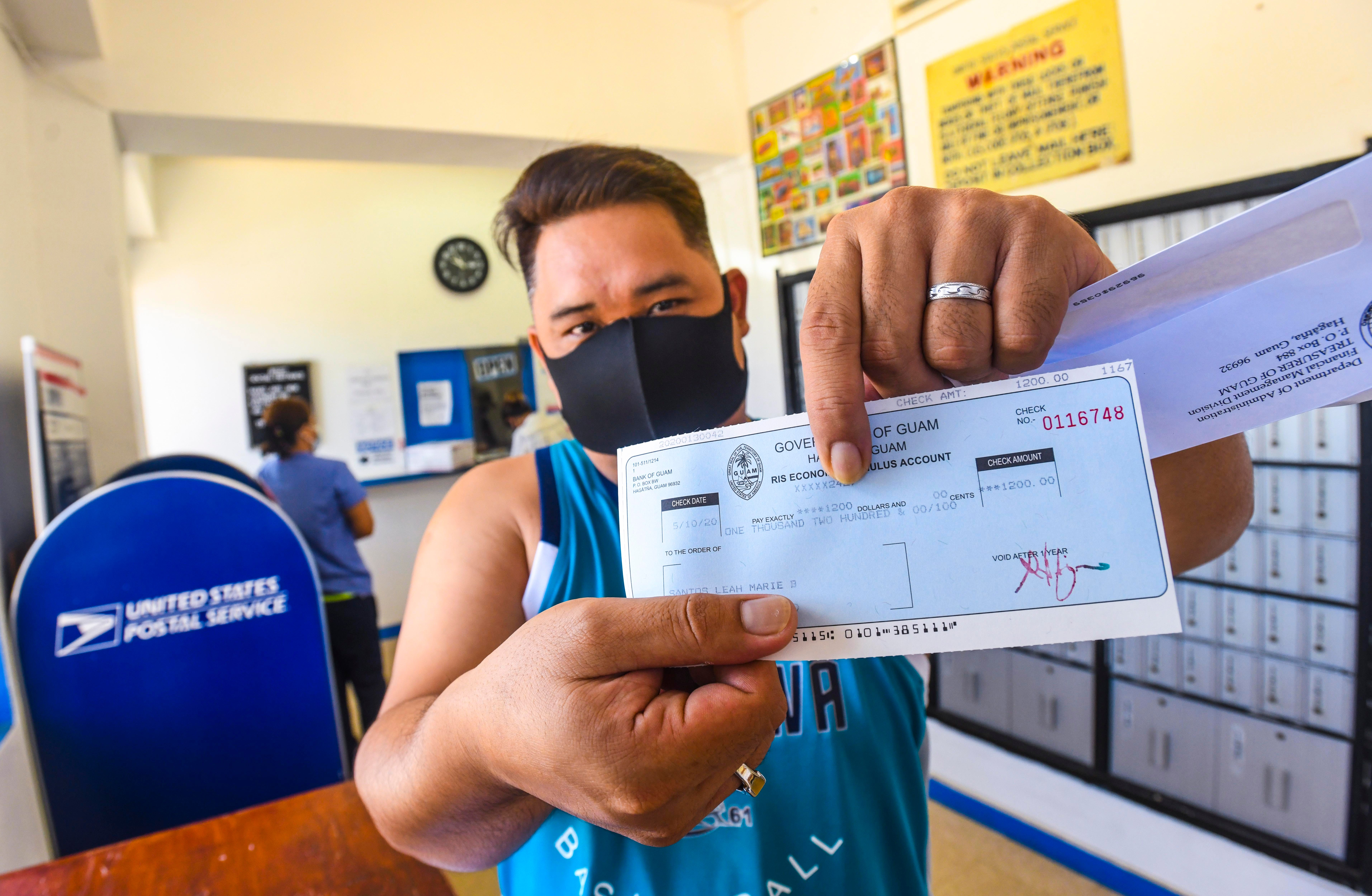 In this May 13, 2020, Yigo resident Leah Santos holds out his Economic Stimulus Payment he received after checking mail at the U.S. Postal Service satellite office in Yigo. President Joe Biden's$1.9 trillion COVID-19 relief proposalwould include stimulus payments of$1,400.