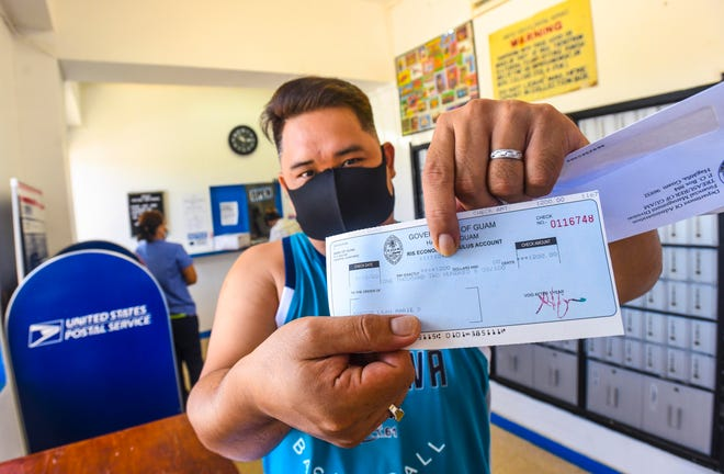 Yigo resident Leah Santos holds out his Economic Stimulus Payment he received after checking his mail at the U.S. Postal Service satellite office in Yigo in this May 13 file photo.