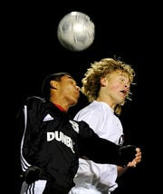 Nick Gregory, right, heads the ball against Dunbar's Guillermo Clemente (9) during the 2012 state soccer semifinal in Lexington.