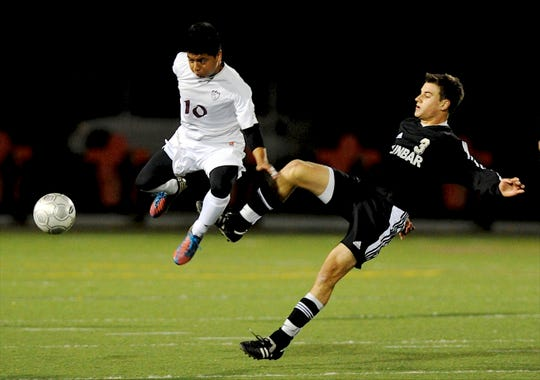 Henderson County's Miguel Velazquez, left, leaps past Dunbar's Caleb Clay, right, as he scurries to gain control during the 2012 state soccer semifinal in Lexington.