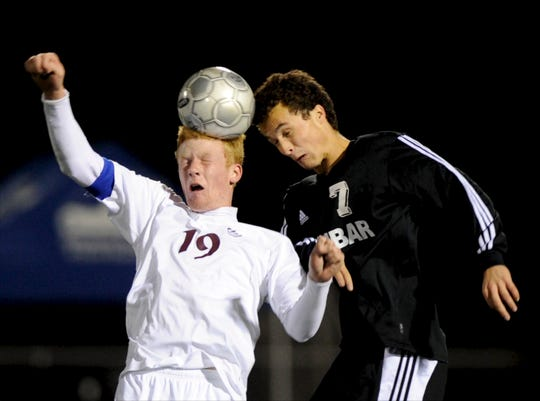 Henderson County's James Bickers (19) heads the ball past Dunbar's Nick Dimeo (7) during the 2012 state soccer semifinals in Lexington.